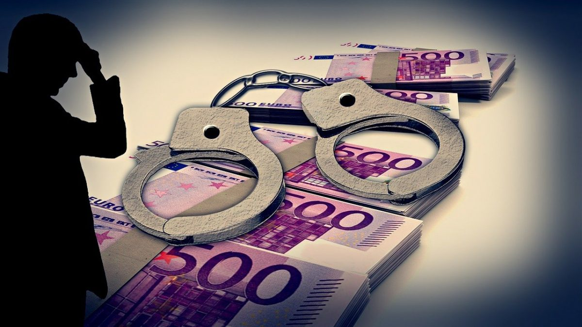 Silhouette of overwhelmed man next to stacks of euros and a pair of handcuffs