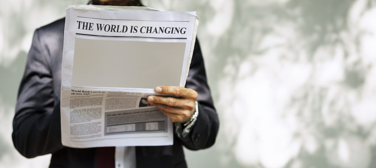 "Man reading newspaper with the headline ""The World is Changing"""